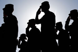 Army troops saluting at sunset