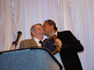 Kevin Lipton (right) kisses John N. Rowe III