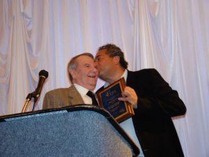 Kevin Lipton (right) kisses John N. Rowe III