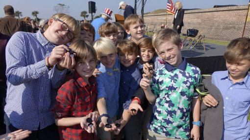 Students from Sullivan's Island Elementary School hold quarter